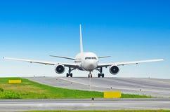Белый самолет пассажира ездя на такси на авиапорте Стоковые Фотографии RF