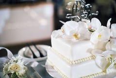 Белый свадебный пирог, 2 украшенного слоя, с белыми орхидеями - взгляд сверху, закрыло вверх Стоковое Изображение RF