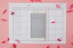 Белый смартфон лежит на бумажном календаре r стоковые фотографии rf