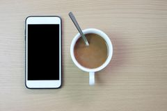 белый смартфон с черным пустым экраном и кружкой белого кофе дальше стоковые изображения rf