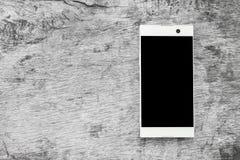 Белый современный мобильный телефон на древесине серого цвета grunge Стоковое Фото
