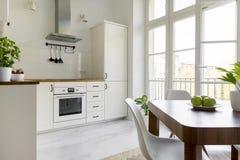 Белый стул на деревянном обеденном столе в wi простой кухни внутренних стоковое фото rf