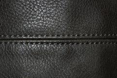 Белый сшитый шов на черной коже стоковые изображения