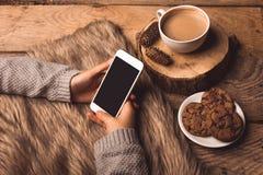 Белый телефон в руках девушки, печений кофе, конусов и меха стоковое изображение rf