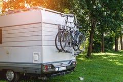 Белый трейлер прикрепленный к велосипеду стоит на расчистке в древесинах на солнечный день Стоковая Фотография RF