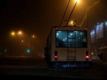 Белый троллейбус управляя опасно в тумане на ноче Стоковое Фото