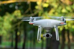 Белый трутень летания с камерой на зеленой предпосылке деревьев стоковое изображение rf