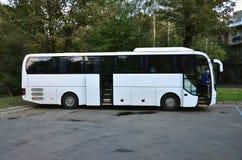 Белый туристический автобус для отклонений Шина припаркована в месте для стоянки около парка Стоковая Фотография