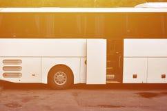 Белый туристический автобус для отклонений Шина припаркована в месте для стоянки около парка Стоковая Фотография RF