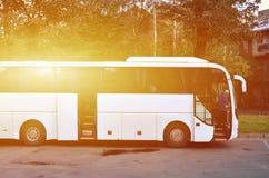 Белый туристический автобус для отклонений Шина припаркована в месте для стоянки около парка Стоковое фото RF