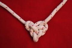Белый узел веревочки на красной предпосылке Стоковое Изображение