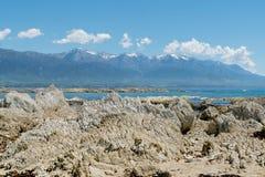 Белый утес вулкана на береге моря с предпосылкой горы Стоковое Фото