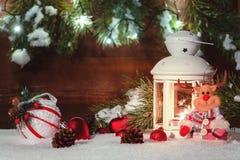 Белый фонарик с горящей свечой стоит в снеге окруженном украшениями рождества на предпосылке деревянного стоковые фотографии rf