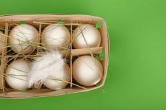 Белый цыпленок eggs в деревянном контейнере над зеленым цветом Стоковое фото RF