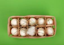 Белый цыпленок eggs в деревянном контейнере над зеленым цветом Стоковое Фото