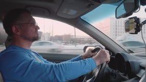 Белый человек в голубом longsleeve управляет автомобилем со зданиями и другими автомобилями на предпосылке акции видеоматериалы
