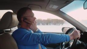 Белый человек медленно управляет автомобилем и пробует поговорить старый телефон кнопки Старомодный телефон Заход солнца на предп сток-видео