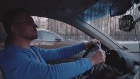 Белый человек управляет автомобилем в городе на высокой скорости сток-видео