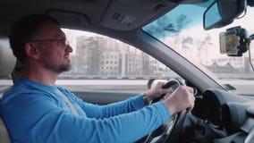 Белый человек управляет автомобилем на высокой скорости и наблюдает видео на смартфоне который висит в держателе телефона акции видеоматериалы