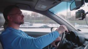 Белый человек управляет автомобилем на дороге города и карты направляют на смартфоне акции видеоматериалы