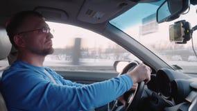 Белый человек управляет автомобилем на шоссе и наблюдает видео пока управляющ Поездка в удобном автомобиле акции видеоматериалы