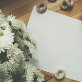Белый чистый лист бумаги для записи, белых цветков и barel на деревянном столе Стоковые Изображения