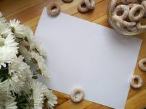 Белый чистый лист бумаги для записи, белых цветков и barel на деревянном столе Стоковые Фото