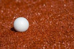 Белый шарик для хоккея игровой площадки на красной предпосылке травы стоковое фото
