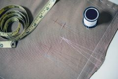 Белый шить поток и лента нежности измеряя на ткани ткани для делать ткань Стоковые Изображения