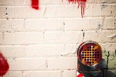 Белыми покрытые граффити решетка и труба стены и вытыхания здания стоковые изображения rf