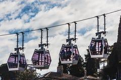4 белых кабины фуникулеров с прозрачными окнами и людьми под коричневыми крышами на голубом небе с белыми облаками стоковое фото