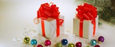 2 белых коробки с красными лентами на предпосылке рождества Стоковые Фото