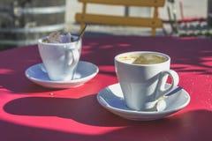 2 белых кофейной чашки на обеденном времени с ложкой Стоковая Фотография