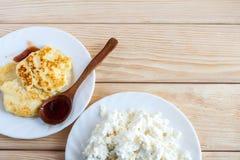 2 белых плиты с свежими творогом и чизкейками с деревянной ложкой с сливой сжимают на деревянном столе с космосом экземпляра Стоковые Фото