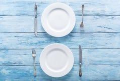 2 белых пустых плиты и столового прибора на голубой таблице Стоковые Изображения RF