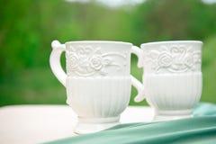 2 белых пустых чашки на таблице против зеленой предпосылки Стоковое Фото