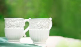 2 белых пустых чашки на таблице против зеленой предпосылки Стоковые Фотографии RF