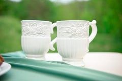 2 белых пустых чашки на таблице против зеленой предпосылки Стоковое фото RF