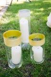3 белых свечи стоят в стеклянных вазах на траве Стоковое Изображение