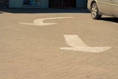 2 белых стрелки дороги Текстурированный серый асфальт Стоковые Изображения RF
