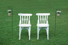 2 белых стуль ждать grooms рядом с некоторым флористическим украшением на зеленой траве Стоковое Фото