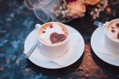 2 белых чашки капучино с сердцами и обручальными кольцами, букетом невесты на таблице Стоковые Фотографии RF