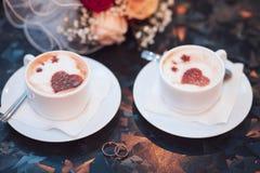 2 белых чашки капучино с сердцами и обручальными кольцами, букетом невесты на таблице Стоковое Изображение