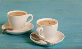 2 белых чашки кофе на деревянной голубой предпосылке Стоковое Фото