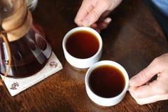 2 белых чашки с кофе в руках на таблице Стоковая Фотография