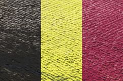 Бельгийский флаг на картине дороги булыжника стоковое фото rf