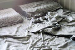 Белье скомканное шелком на кровати Стоковое фото RF