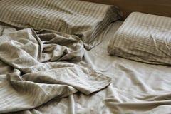 Белье скомканное шелком на кровати Стоковые Изображения RF