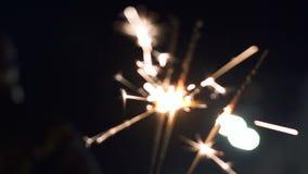 Бенгальские огни фейерверка освещая на партии Нового Года outdoors, конец вверх, праздники сток-видео