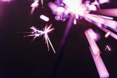 Бенгальский огонь Бенгалии сирени освещает на черной предпосылке в честь торжеств Нового Года и дня рождения рождества Стоковое фото RF